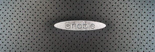 Metallplakette mit Logo auf Rückenlehne.